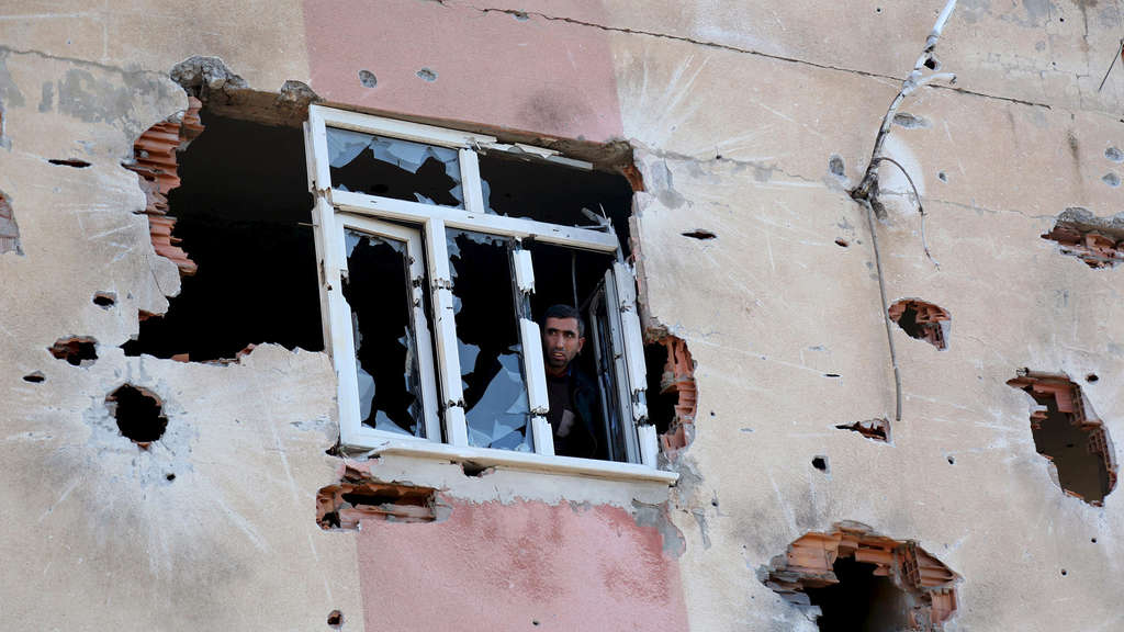 A man looks out of a building which was damaged during the security operations and clashes between Turkish security forces and Kurdish militants, in Sur district of Diyarbakir, Turkey, December 11, 2015. REUTERS/Sertac Kayar TPX IMAGES OF THE DAY - RTX1Y9U9 n