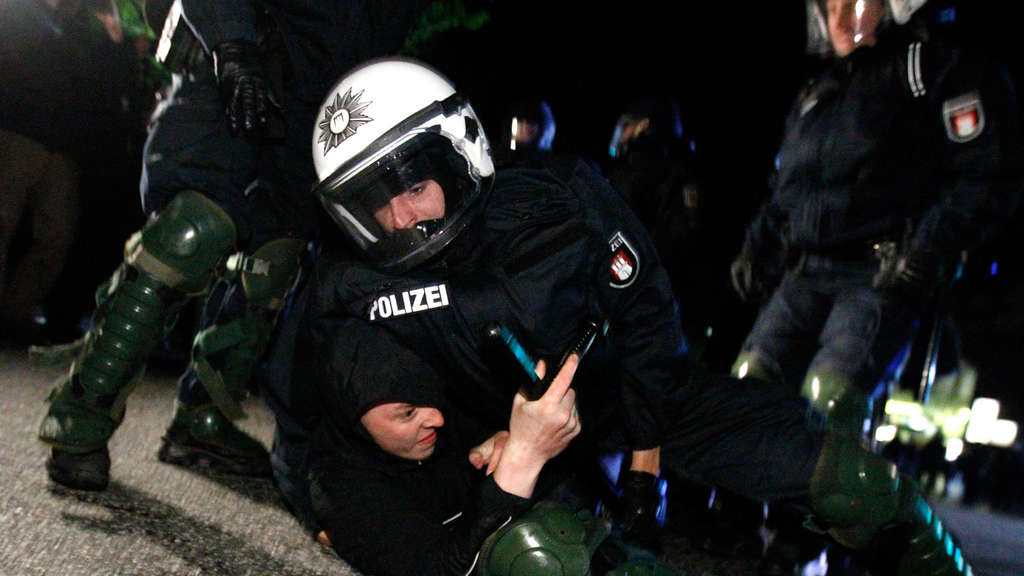 A riot policeman detain a left-wing protestor during May Day demonstrations in Hamburg May 1, 2011. REUTERS/Thomas Peter (GERMANY - Tags: POLITICS CIVIL UNREST) - RTR2LVIO n