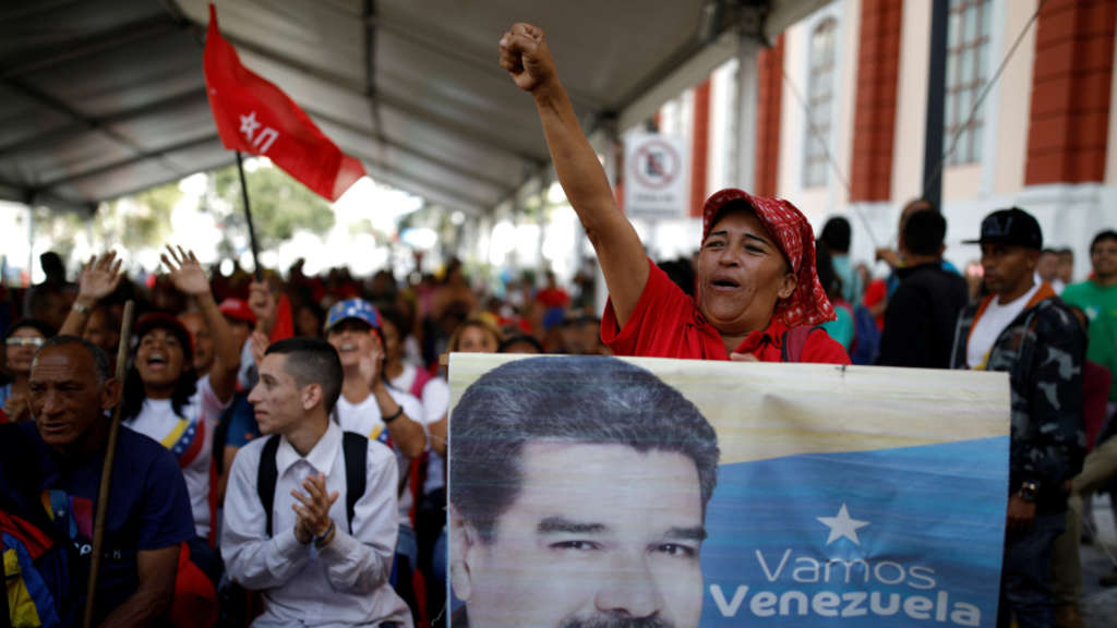 A supporter of Venezuela&#39s President Nicolas Maduro holds a banner depicting him as he takes part in a gathering outside the Miraflores Palace in Caracas,