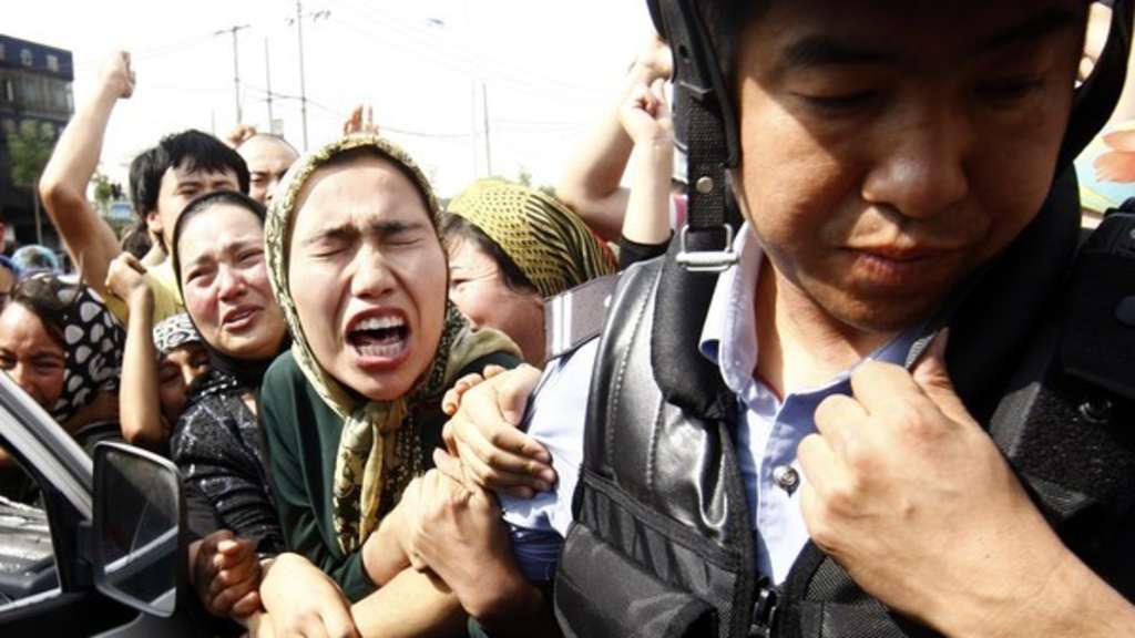 Eine Angehörige der uigurischen Minderheit in China versucht einen Polizisten zu packen, während einer Demonstration in Ürümqi in der Unruheregion Xinjiang in Nordwestchina.