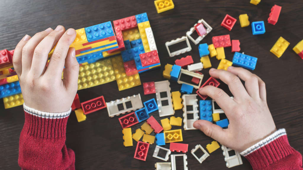 Children s hands playing with building bricks on a table model released Symbolfoto PUBLICATIONxINxGE
